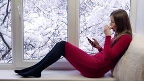 Ładna dziewczyna w czerwieni sukni obsiadaniu na windowsill, pić kawowym i używać smartphone, na zewnątrz zimy zbiory wideo