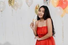 Ładna dziewczyna w czerwieni zabawę przy przyjęciem zdjęcie stock