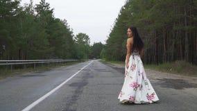 Ładna dziewczyna w długiej pięknej sukni chodzi na drodze zdjęcie wideo