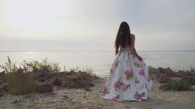 Ładna dziewczyna w długiej pięknej sukni chodzi rzeką zbiory wideo