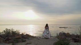 Ładna dziewczyna w długiej sukni na pięknej plaży zbiory wideo