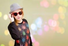 Ładna dziewczyna w galanteryjnych okularach przeciwsłonecznych na kolorowym bokeh Zdjęcia Stock