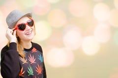 Ładna dziewczyna w galanteryjnych okularach przeciwsłonecznych na kolorowym bokeh Obrazy Stock