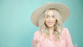 Ładna dziewczyna w kapeluszu na turkusowym tle, fotografuje zdjęcie wideo