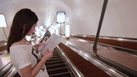 Ładna dziewczyna w metrze Młoda kobieta patrzeje mapę na eskalatorze iść up z długim ciemnym włosy zdjęcie wideo
