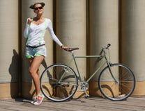 Ładna dziewczyna w skrótach i koszulce, w okularów przeciwsłonecznych stojakach z rowerową dylemat przekładnią pozować przeciw tł Zdjęcia Stock