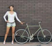 Ładna dziewczyna w skrótach i koszulka stojakach z rowerową dylemat przekładnią blisko ściana z cegieł jaskrawy słoneczny dzień Fotografia Stock