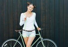 Ładna dziewczyna w skrótach i koszulka stojakach z rowerową dylemat przekładnią blisko ściany drewnianych desek jaskrawy słoneczn Zdjęcie Royalty Free