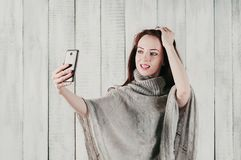 Ładna dziewczyna w szarym pulowerze uśmiecha się selfie i robi, zdjęcia royalty free