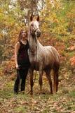 Ładna dziewczyna z długie włosy pozycją obok zadziwiającego konia w autum Obraz Royalty Free