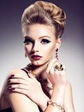 Ładna dziewczyna z piękną fryzury i złota biżuterią, jaskrawy m zdjęcia stock