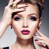 Ładna dziewczyna z pięknej twarzy jaskrawym makijażem i złoto biżuterią zdjęcia stock