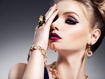 Ładna dziewczyna z pięknej twarzy jaskrawym makijażem i złoto biżuterią obraz royalty free