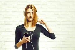 Ładna dziewczyna z słuchawki i telefonem obraz stock
