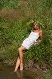 Ładna dziewczyny młoda kobieta z naturalną blond długie włosy, piękną twarzą w i siedzi na rzeki plaży dalej obraz stock