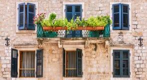 Ładna europejczyka domu fasada z nadokiennymi żaluzjami, balkonem i puszkować roślinami, zdjęcia stock