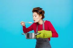 Ładna gospodyni domowa wącha gorącą domowej roboty polewkę i kosztuje przy kuchnią obraz royalty free