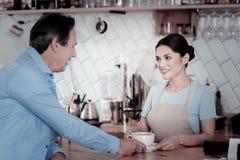 Ładna kelnerka opowiada ono uśmiecha się i gość zdjęcie stock
