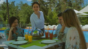 Ładna kelnerka przynosi smakowitego naczynie firma cztery przyjaciela blisko basenu zbiory wideo