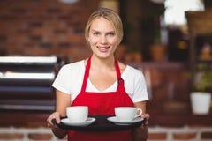 Ładna kelnerka trzyma tacę z kawami Obraz Royalty Free