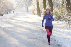Ładna kobieta Jogging w zimie z słuchawkami obraz stock