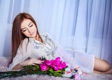 Ładna kobieta kłaść z kwiatami obraz royalty free