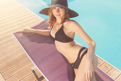 Ładna kobieta kłama blisko basenu Fotografia Stock