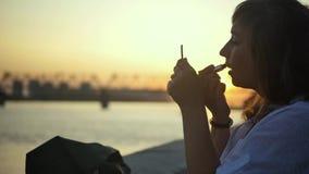 Ładna kobieta maluje jej wargi z pomadką podczas gdy patrzejący w małym lustrze na tle zmierzch na rzece zbiory wideo