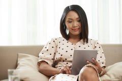 Ładna kobieta odpoczywa na kanapie zdjęcia stock