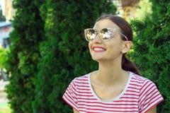Ładna kobieta ono uśmiecha się nad kolorowym tłem w modnych okularach przeciwsłonecznych zdjęcia royalty free