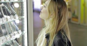 Ładna kobieta patrzeje dla nowego smartphone zbiory