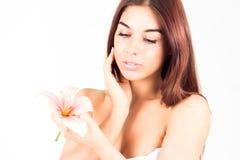 Ładna kobieta patrzeje różowej lelui i wzruszającego policzka z czystą skórą 20 piękna wieka wystawy retrospektywnej przeglądu s  Fotografia Royalty Free