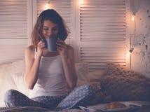 Ładna kobieta pije kawowego obsiadanie na łóżku w domu Obrazy Stock