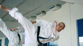 Ładna kobieta pokazuje karate sztuczkę blisko lustra w gym zbiory