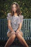 Ładna kobieta pozuje na ławce Zdjęcie Stock