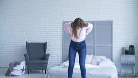 Ładna kobieta próbuje przymocowywać drelich w jej sypialni zbiory wideo