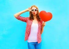 Ładna kobieta robi lotniczemu buziakowi z czerwonym balonem w kształcie Zdjęcie Stock