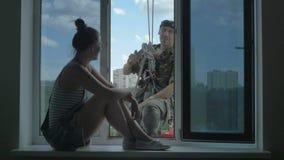 Ładna kobieta siedzi na rozmowach z steeplejack na zewnątrz okno i windowsill zbiory wideo