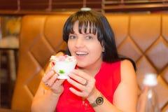 Ładna kobieta siedzi przy cukiernianą restauracją fotografia stock