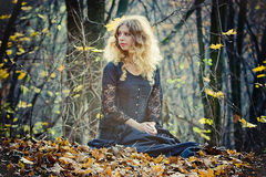 Ładna kobieta siedzi w czarodziejskim drewnie zdjęcie royalty free