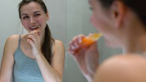 Ładna kobieta szczotkuje jej zęby w łazience w ranku Ranek higiena zbiory wideo