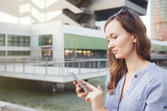Ładna kobieta trzyma mądrze telefon, używać mapy zastosowanie dla znajdować lokacja adres Zdjęcie Royalty Free