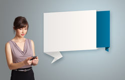 Ładna kobieta trzyma telefon i przedstawia nowożytną origami kopię Zdjęcia Stock