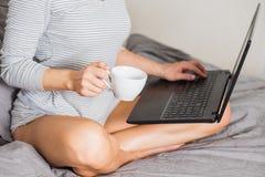 Ładna kobieta używa laptop podczas gdy mieć filiżanka kawy na łóżku zdjęcie stock