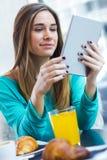 Ładna kobieta używa pastylkę podczas gdy mieć śniadanie w sklep z kawą Fotografia Royalty Free