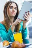 Ładna kobieta używa pastylkę podczas gdy mieć śniadanie w sklep z kawą Zdjęcie Royalty Free
