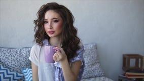 Ładna kobieta ubierał w piżama napojów ranku kawie w jej sypialni zbiory wideo