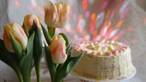 Ładna kobieta wącha jej wazę tulipany i ono uśmiecha się przy kamerą w kuchni w domu zbiory
