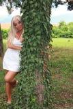 Ładna kobieta w biały smokingowy opierać przeciw drzewu Zdjęcie Stock