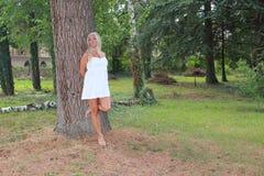 Ładna kobieta w biały smokingowy opierać przeciw drzewu Zdjęcia Stock